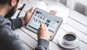 Mann mit Tablet liest Fake News