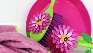 Putzutensilien wie Tuch und Besen in pink, mit Blumen verziert