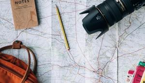 Reiseutensilien (Plan, Kamera, Notizblock, Stift)