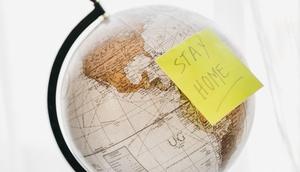 """Globus mit Post-it mit der Aufschrift """"Stay home"""""""