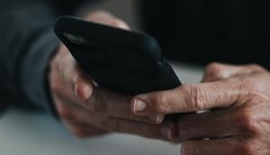 Männerhände halten ein Handy