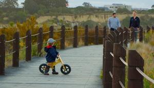 Kind mit Laufrad auf Holzsteg, 2 Erwachsene im Hintergrund