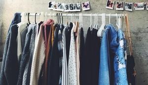 mehrere Kleidungsstücke auf Bügeln und Kleiderstange