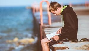 Jugendlicher sitzt am Meer und liest