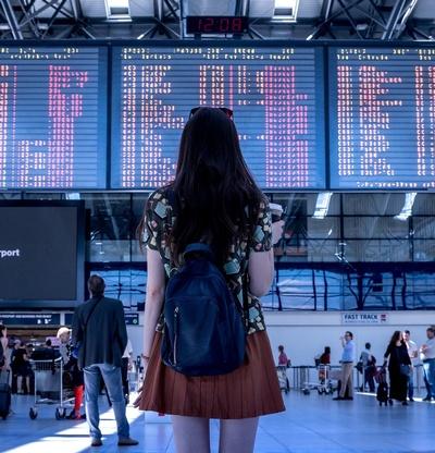 Frau steht vor Anzeigetafel am Flughafen