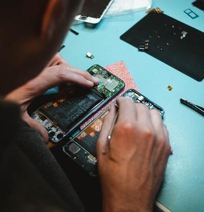 Mann repariert Handy, das offen vor ihm liegt