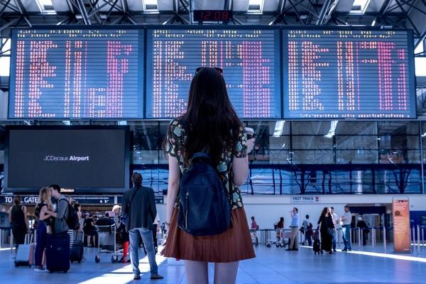 Frau steht vor Anzeigetafel am Flughafen, © Photo by Jan Vašek on Pixabay