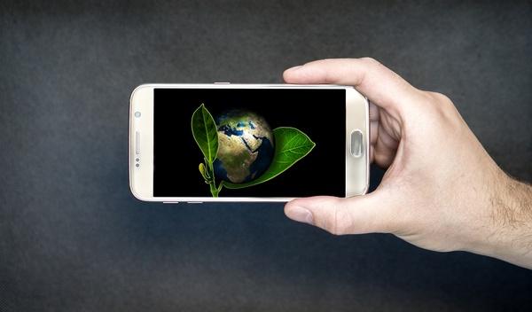 Ein Handydisplay zeigt die Erde, die mit Blättern umgeben ist., © Bild von Gentle07 auf Pixabay.
