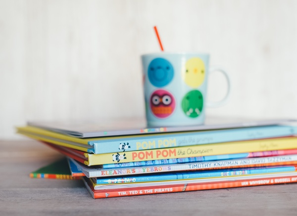 Kinderbuch mit einer Tasse oben auf dem Stapel, © Photo by Annie Spratt on Unsplash