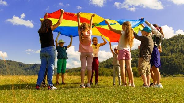 Kinder spielen im Kreis mit buntem Tuch , ©  Artem Kniaz on Unsplash