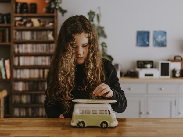 Junges Mädchen wirft Geldmünze in eine Spardose in Form eines VW-Busses, © Annie Spratt on Unsplash