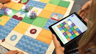 Kinder beim Spielen mit Tablet und Bee Bot