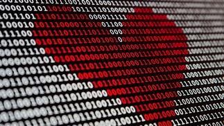 Bildschirm aus binären Codes, dem sich ein rotes Herz abzeichnet
