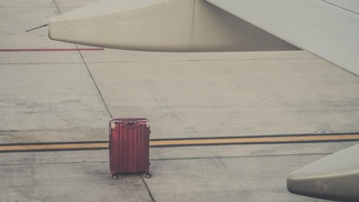 alleinstehender Koffer am Flugfeld