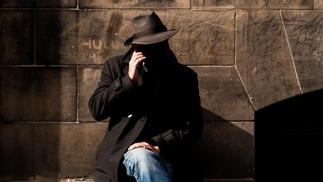 Mann mit Hut sitzt auf einer Bank und telefoniert mit dem Handy