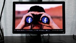 Person schaut durch Fernglas mit Facebook-Logo