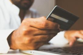 Männerhand sitzt vorm Notebook mit Kreditkarte in der Hand
